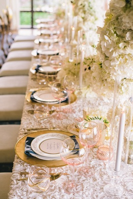 Wedding reception place setting with wine glasses with pink bowls and double old-fashioned glass