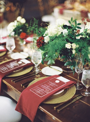 wedding reception dark wood table gold plate burgundy red napkin acrylic menu greenery centerpieces