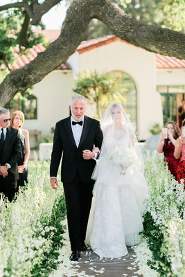 bride in carolina herrera ball gown in blusher veil walking with her father down the aisle