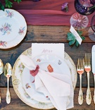 patterned china and gold flatware on wooden farm table