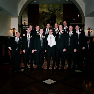 Groom with men in wedding party in black and grey suits