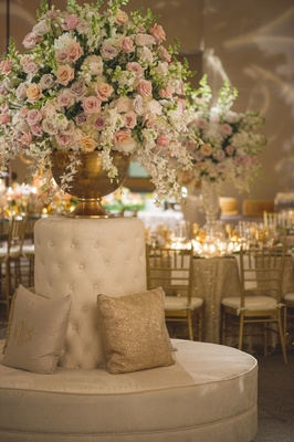 Wedding reception with round sofa, glittery throw pillow, gold urn with orchids, roses, snapdragons