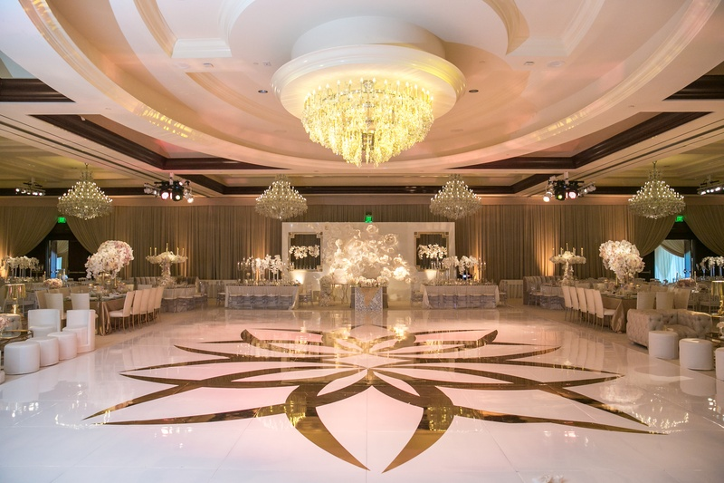 custom white dance floor with gold design, chandelier above