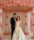 Bride and groom under opulent pink chuppah