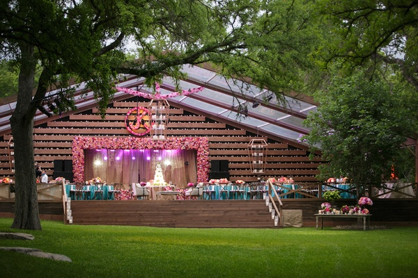 Rustic wedding reception structure with multi-level wood and glass lanterns with white candles