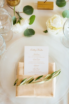 place setting with neutral hued napkin, olive sprig, menu