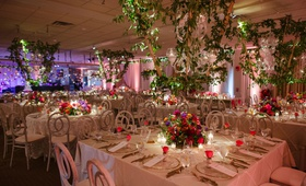 Wedding reception ballroom large lanterns gold square round tables pink flowers roses greenery
