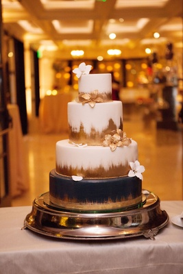 Wedding cake white with gold brush stroke black bottom sugar flowers in white and gold ballroom