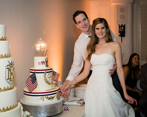 Bride and groom by wedding cakes tall white gold cake and groom cake with american flags olympics
