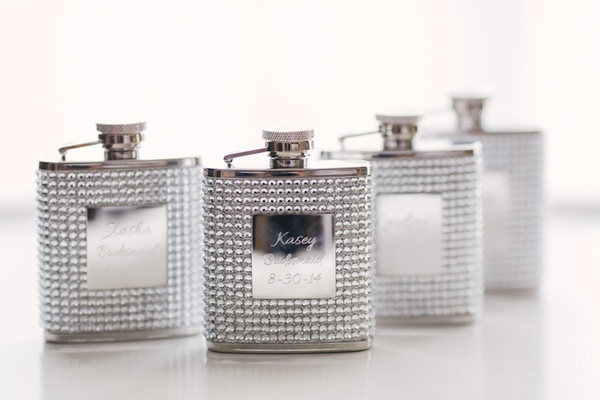 Metal flasks covered in rhinestones and engraved with bridesmaids' names and wedding date