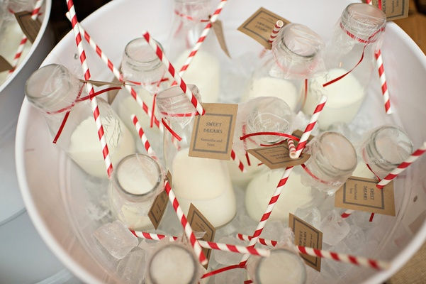 Wedding reception favors of milk in old-fashioned bottles with red and white swirl straws
