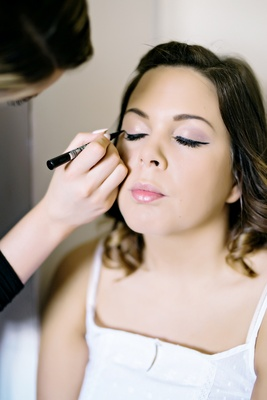 bride getting made up before wedding pink eyeshadow blush lips lipstick lipgloss eye liner