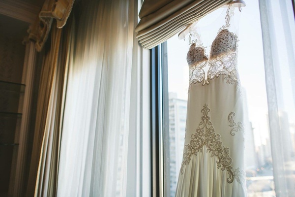 Michal Medina wedding dress from dimitra's bridal couture hanging in window chicago wedding