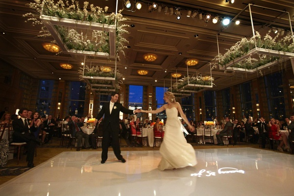 Bride spins on wedding dance floor with plants hanging from ceiling