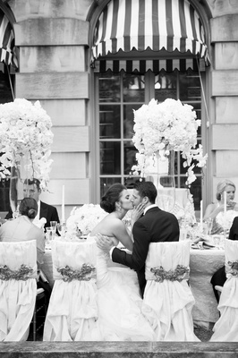 Black and white photo of wedding reception bride and groom kissing at chairs nuage designs interlace