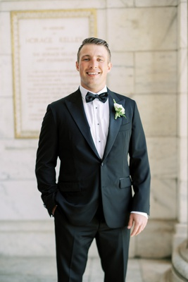 groom in icon custom suit tuxedo black button and bow tie ivory boutonniere cleveland wedding