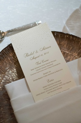 a champagne-colored reception menu with gold calligraphy on white tablescape