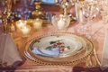 Gold-rimmed glassware and floral china plate
