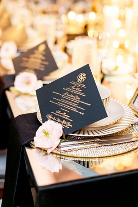 black menu cards with gold calligraphy and a single blush blossom
