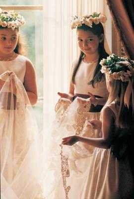 Three flower girls wearing rose crowns hold the brides veil