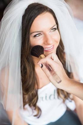 bride wearing veil gets makeup applied