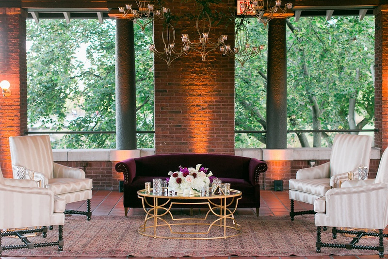 Wedding reception brick walls chandeliers gold coffee table velvet sofa settee armchairs lounging