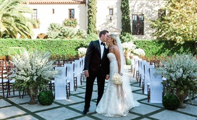 Groom in tuxedo and bride in Monique Lhuillier gown at ceremony