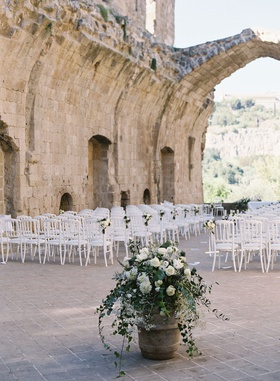 outdoor wedding reception in old building ruins italy countryside white chairs white flowers verdure