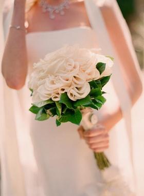 Bride holding monochromatic flowers