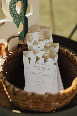 basket of wedding ceremony programs with world map in gold on the top