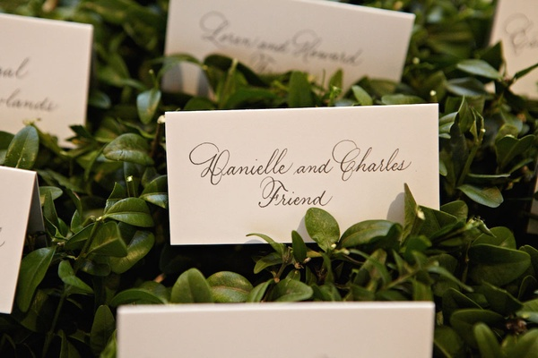 Escort cards on green leaves with black hand lettering