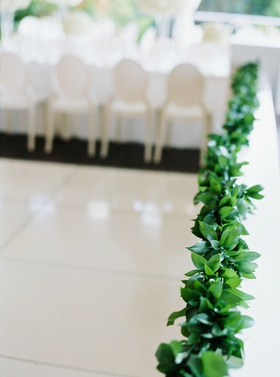 garland of greenery lining the border of the wedding reception tent