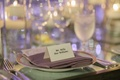 Lavender napkin on top of wedding table with simple tent escort card