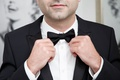 groom in tuxedo wedding day tighten bow tie wedding day accessories