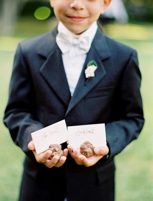 Ring bearer in a dark suit and bow tie holding pinecone place card holders