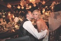Simone Harouche, designer and fashion stylist, is kissed by her groom at reception
