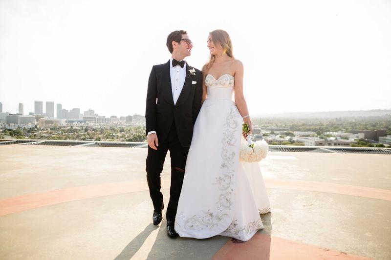 Bride in Oscar de la Renta wedding dress and groom in tuxedo on Los Angeles rooftop portrait photo