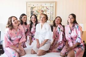 bride bridesmaids laughing pink robes white flower getting ready silk hair makeup california wedding