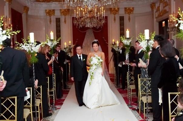 Bride walks down aisle at ballroom wedding