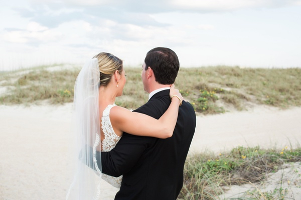 back bride in alon livne lace dress and groom in hugo boss suit with arms around each other beach