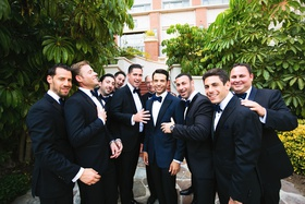 Groom in navy blue suit and bow tie with groomsmen in black suits with navy blue bow ties