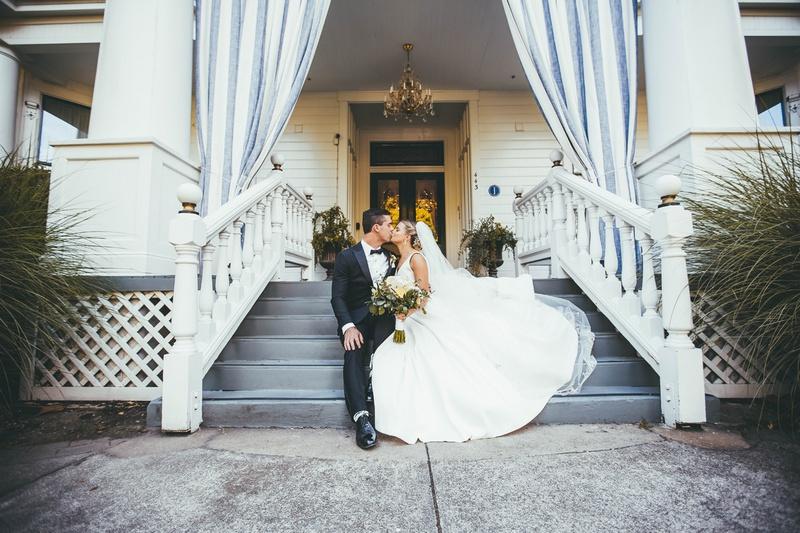 bride in stella york kissing groom on porch steps of white house napa valley inn