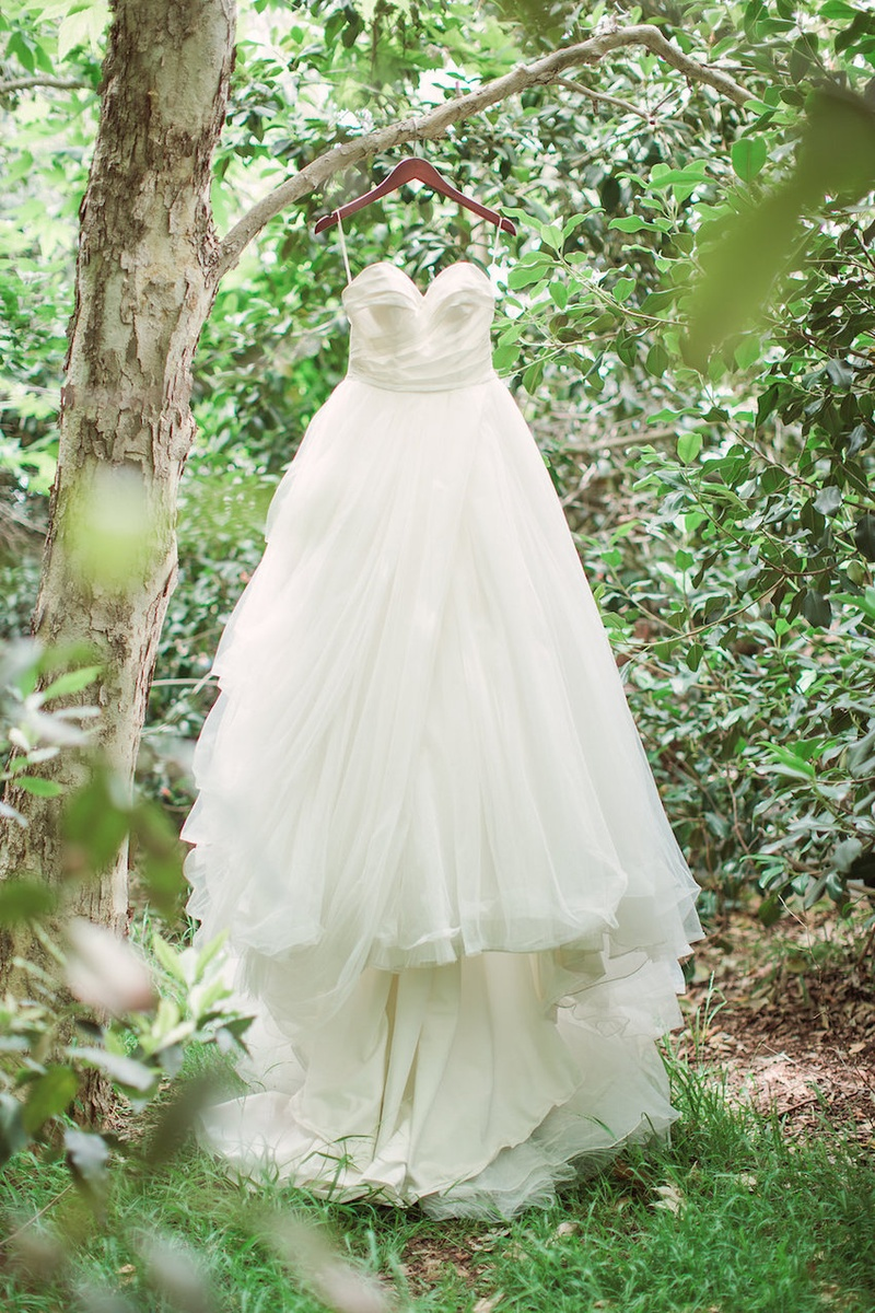 Strapless ball gown wedding dress by Anne Barge with sweetheart neckline, ruching, tulle skirt
