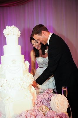 Bride and groom cut ivory wedding cake with purple lighting