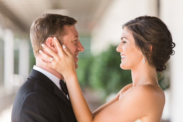 bride holds grooms head look at each other