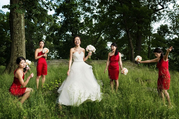 Bride in a strapless Monique Lhuillier gown with bridesmaids in short red Calvin Klein dresses