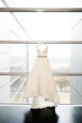 Clinton Library wedding dress hanging up on window ball gown deep neckline crystal belt sash train