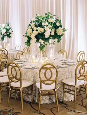 Wedding reception ballroom gold chairs lace table linen tall centerpiece greenery white orchids