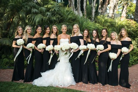 large group of bridesmaids in black off-the-shoulder katie may gown, bride in gemma vera wang