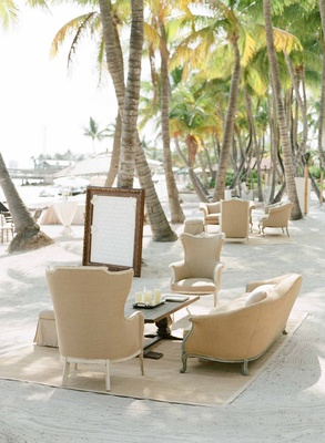 Antique style armchair and sofa on bamboo rug on sand at beach wedding cocktail hour